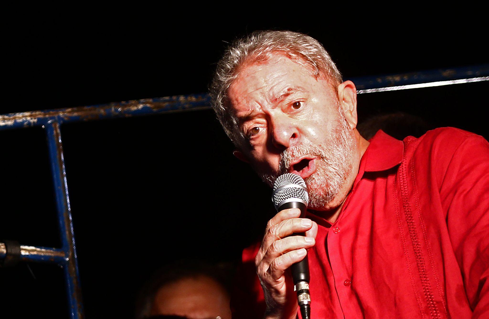 #pracegover O ex-presidente da República, Luiz Inácio Lula da Silva, discursa, segurando um microfone e usando uma camiseta vermelha, em evento contra o impeachment na Avenida Paulista