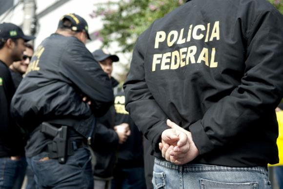 #pracegover: foto mostra agentes da PF de costas, tendo em primeiro plano o nome da jaqueta de um deles com Polícia Federal