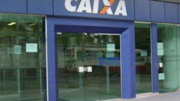 #pracegover: foto mostra fachada de uma agência da Caixa Econômica Federal em azul com o nome do banco em destaque CAIXA