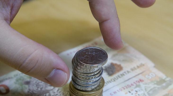 #pracegover: foto mostra uma mão em direção a uma pilha de moedas de R$1 e R$ 0,50 sob duas notas de R$ 50