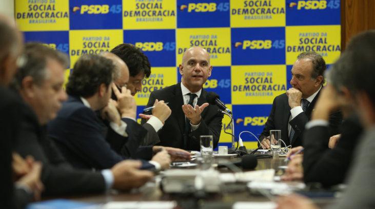 #pracegover: foto mostra bancada de deputados do PSDB sentados em reunião na Câmara e em destaque painel em amarelo e azul com sigla PSDB