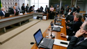 #pracegover: Ataídes de Oliveira está sentado na Comissão de Transparência no Senado com outros parlamentares. Em frente a ele, bancada com outros senadores