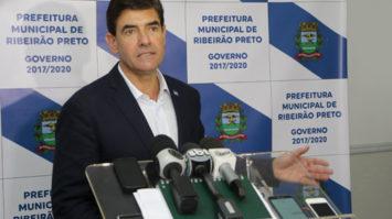 #pracegover: foto mostra prefeito Duarte Nogueira dando coletiva de imprensa. Ele está em pé, na sua frente um púlpito segurando vários microfones e atrás um panei branco e azul