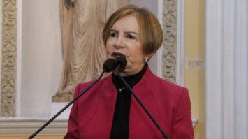#pracegover: Terezinha Nunes está de blusa preta e paletó vermelho falando no microfone no púlpito na Assembleia de PE