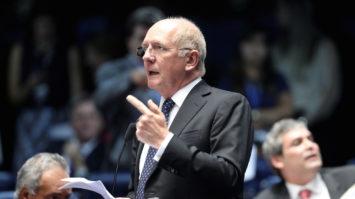 #pracegover: foto mostra o senador Paulo Bauer em pé, falando ao microfone. Ele gesticula a mão esquerda com dedo indicador apontado e na outra, segura papeis