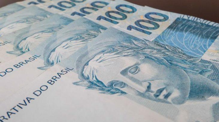 #pracegover: foto mostra cinco cédulas de R$ 100 empilhadas
