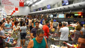 #pracegover: foto ampla mostra supermercado lotado e com filas nos caixas