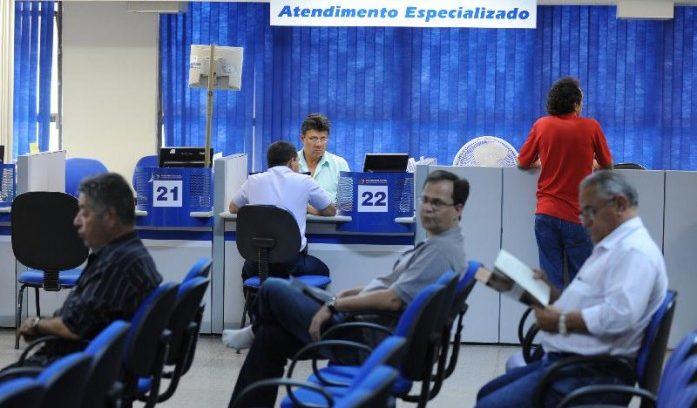 #pracegover: foto mostra agência do INSS, com três pessoas sentadas aguardando para serem atendidas em primeiro plano. Atrás um homem em pé no guichê e outro sentado sendo atendido por profissional do INSS